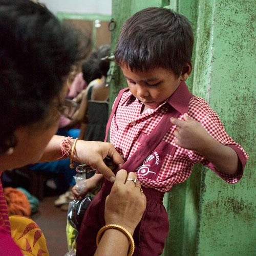 Eine Lehrerin hilft einem Bub mit seiner Uniform.