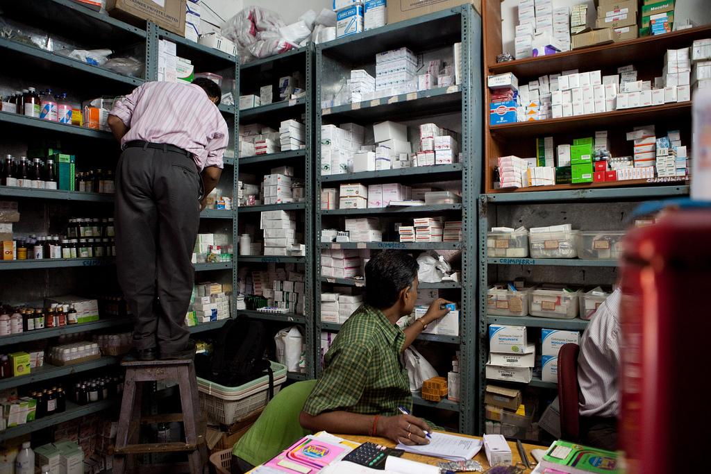 Mitarbeiter in der Apotheke vor de Regalen voller Medikamente.
