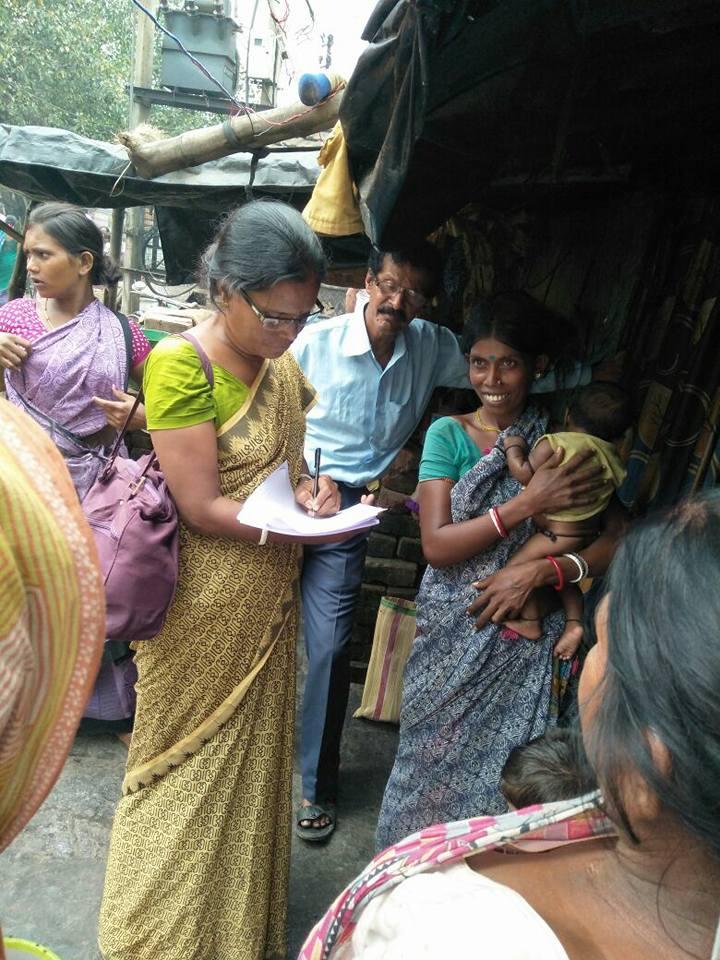 Eine Sozialarbeiterin befragt im Rahmen der Bekämpfung der Unterernährung eine junge Mutter mit einem Baby auf dem Arm zu den Essgewohnheiten der ganzen Familie.