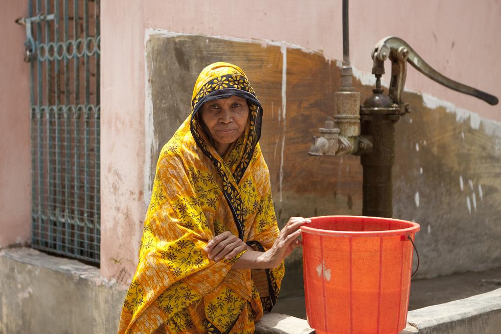 Eine Frau holt sicheres Wasser von dem neuen Brunnen.