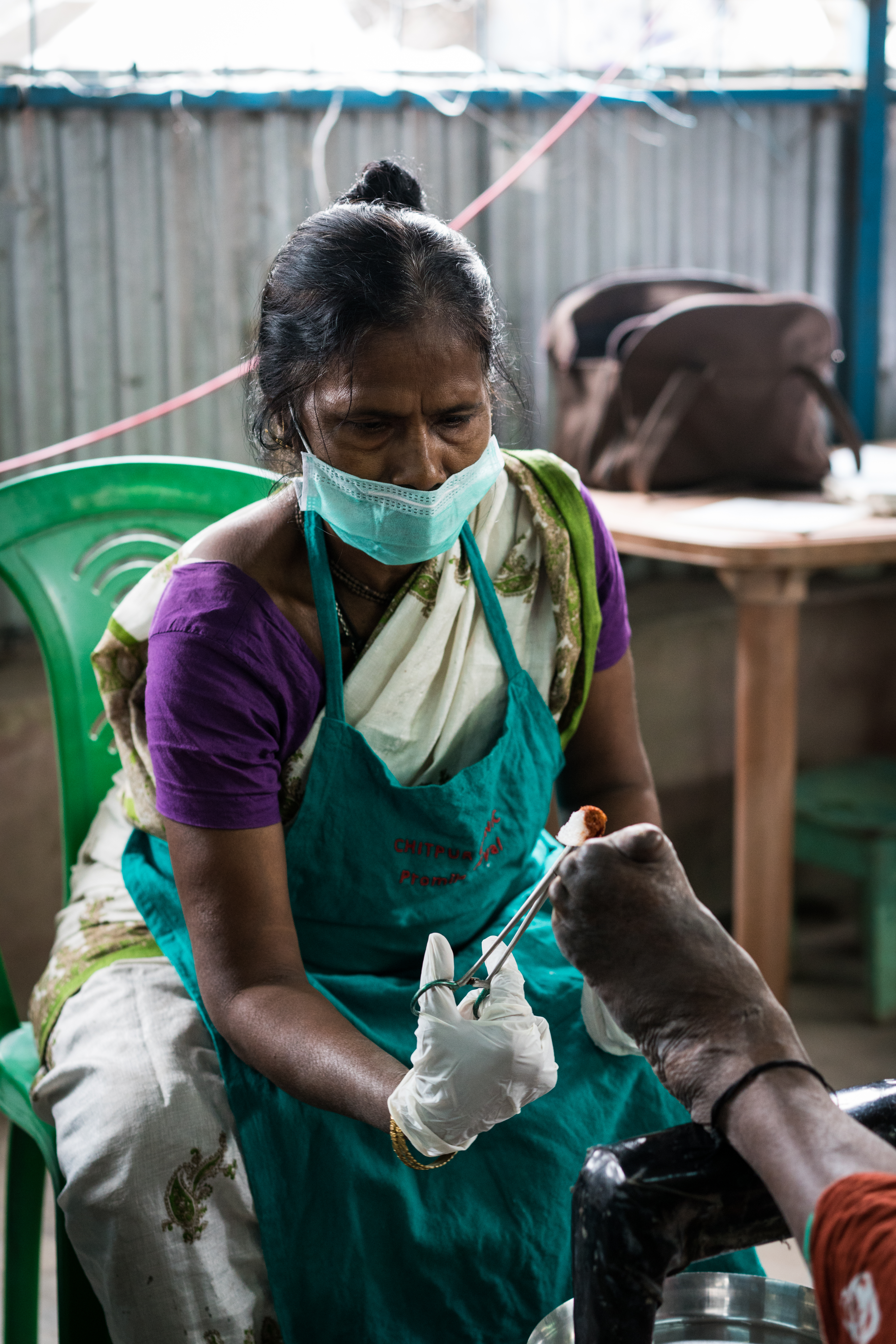 Eine medizinische Mitarbeiterin versorgt die Wunden am Fuss eines Leprakranken.