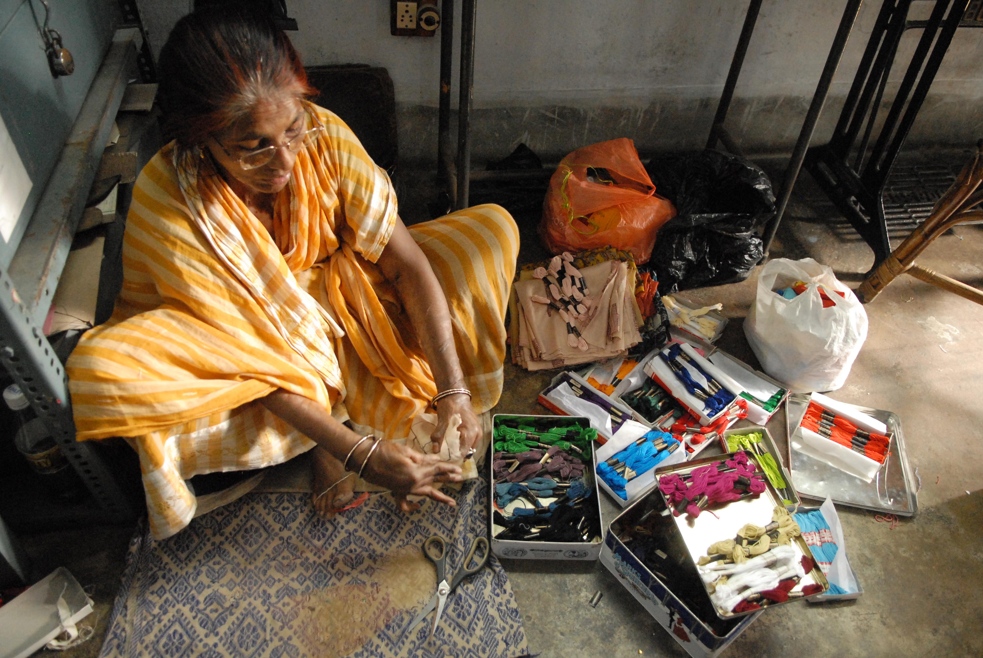 Eine Frau sitzt am Boden und arbeitet an den Handarbeitsprodukten.