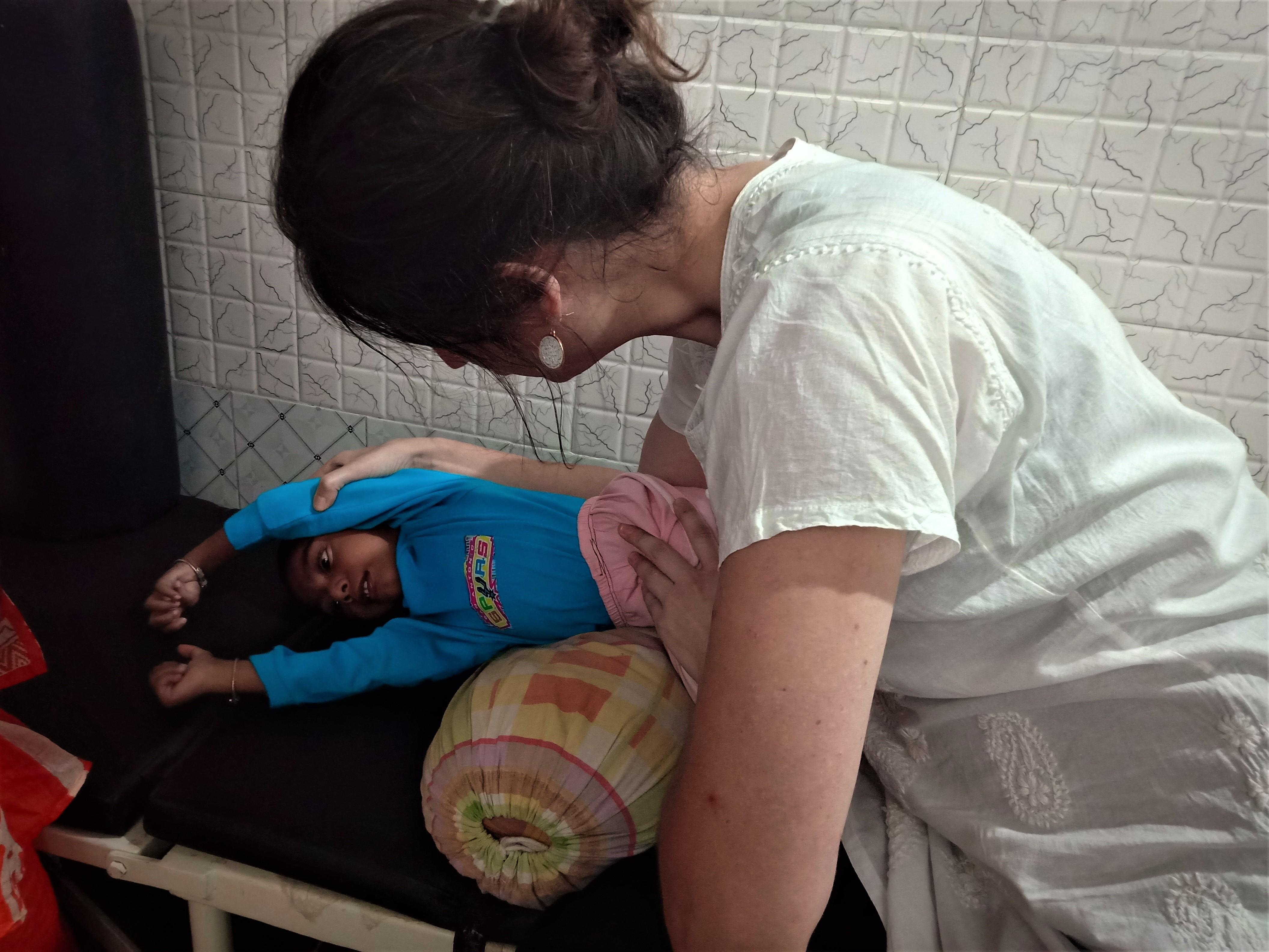 Die Physiotherapeutin Alex behandelt ein kleines Kind mit einer Behinderung.