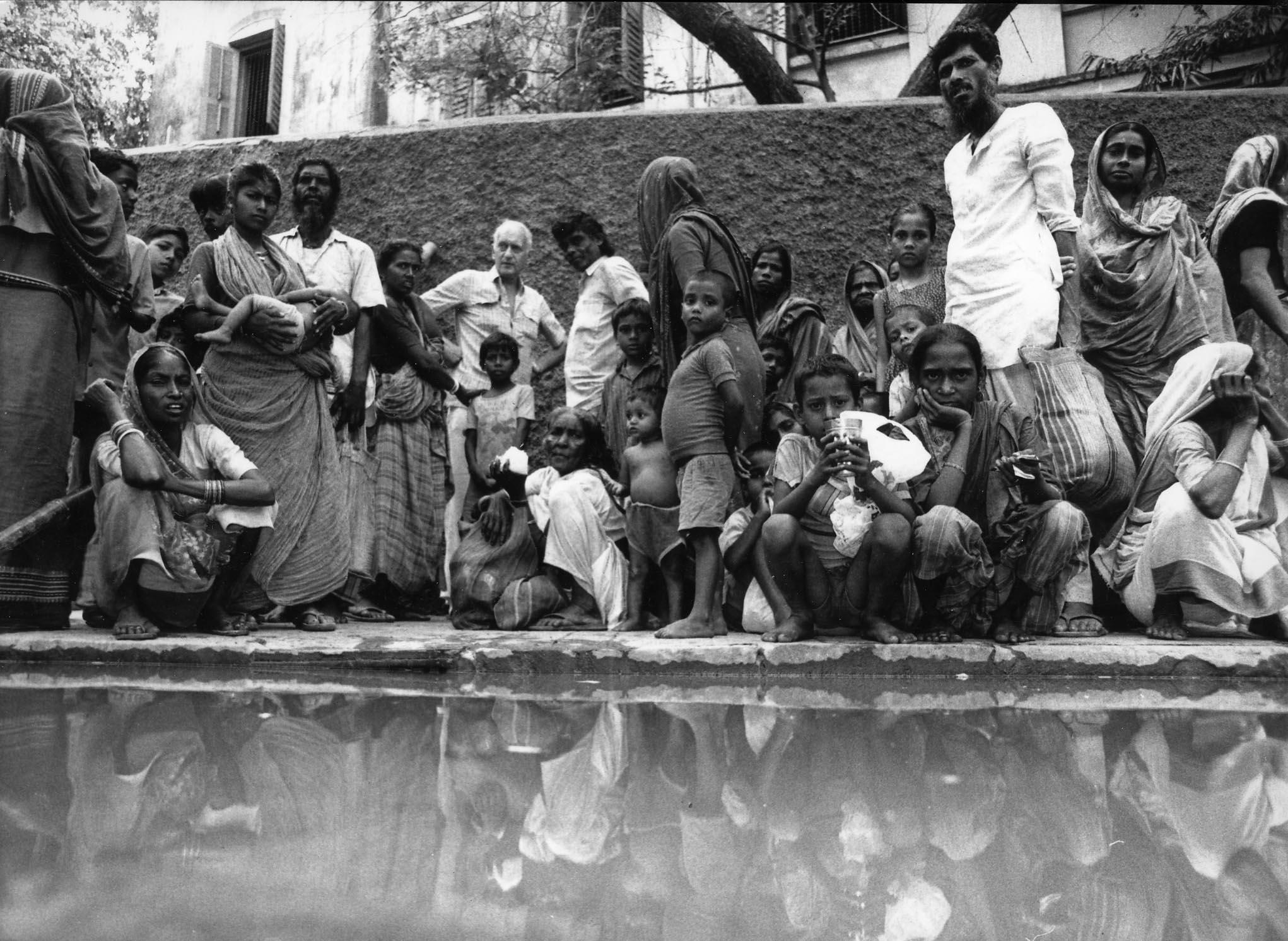 Dr. Jack Preger umringt von bedürftigen Slumbewohnern in Kolkata.