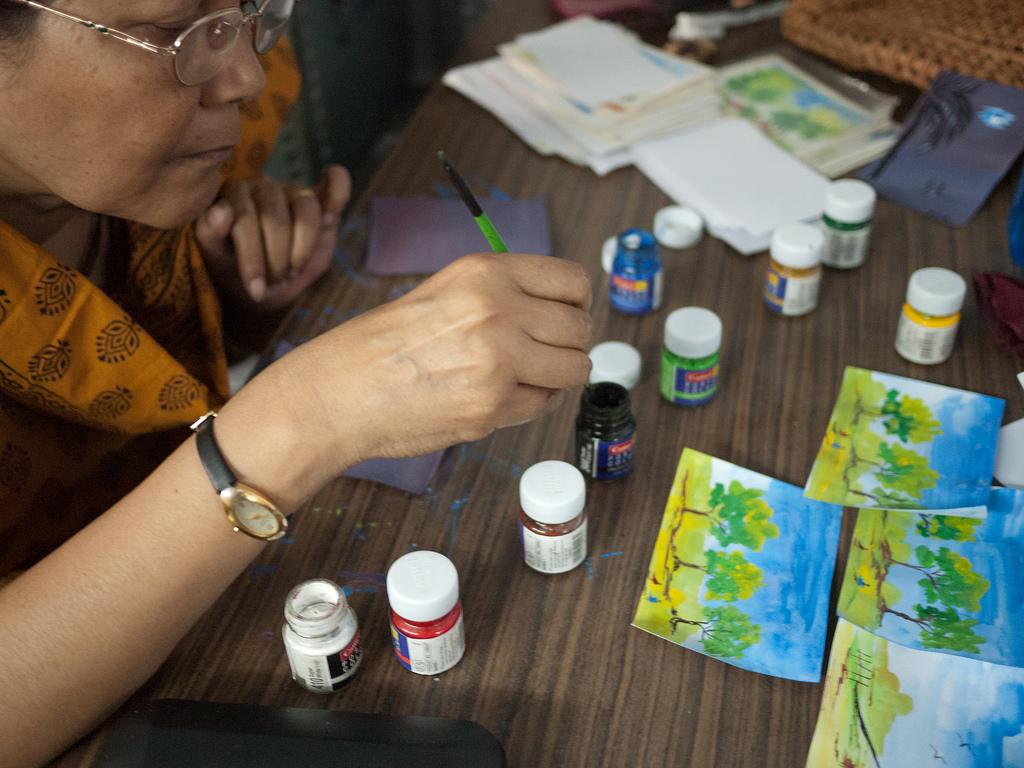 Eine Frau bemalt in der Handicraft-Werkstatt Postkarten.