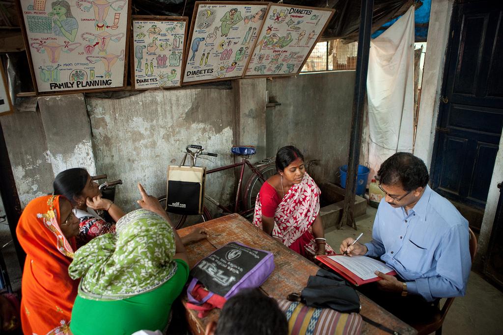 Eine Frau ist in der Konsultation bei einem Arzt, im Hintergrund sind die Plakate, welche für die Familienplanung verwendet werden.