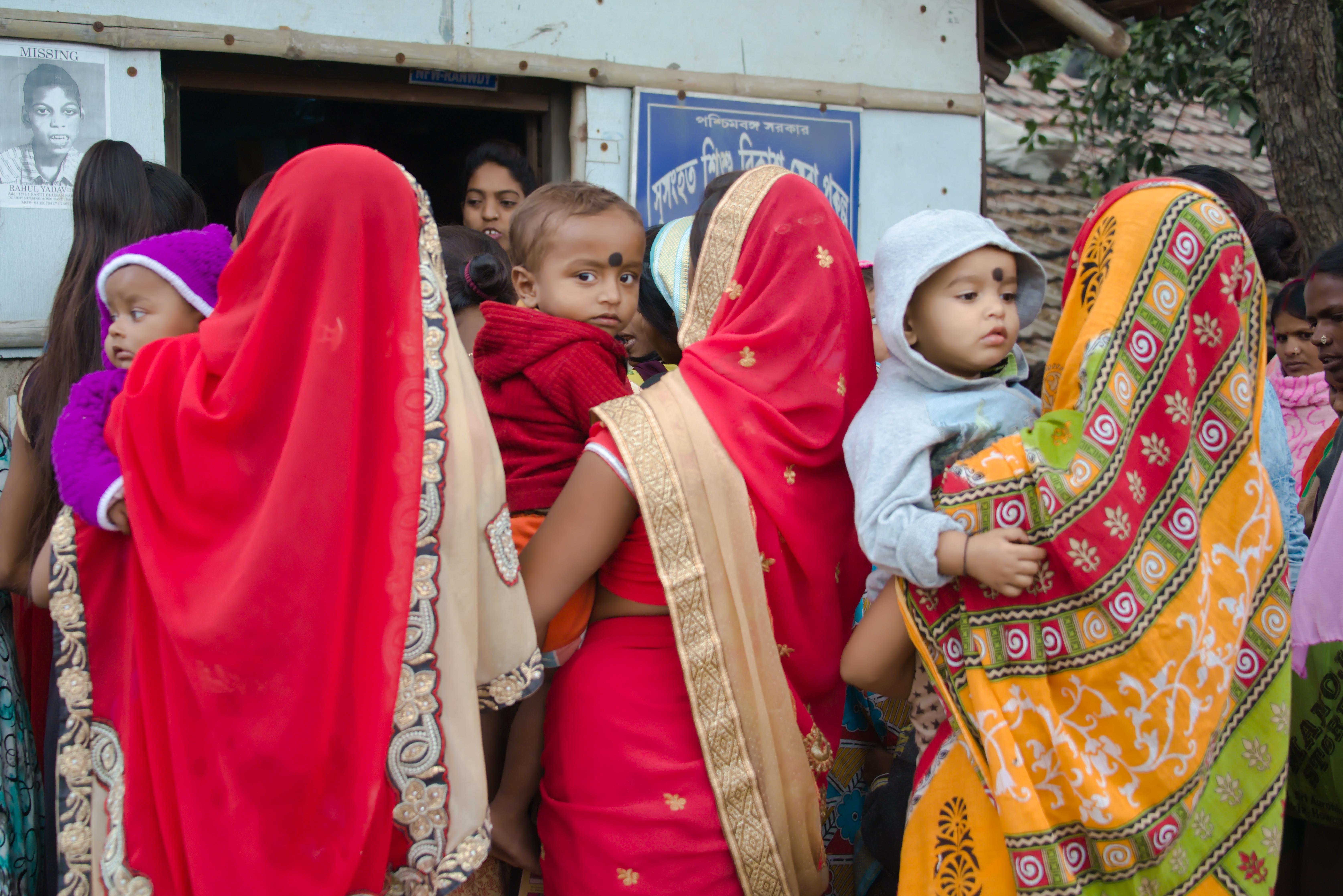 Drei in Saris gehüllte Frauen warten mit ihren Kindern auf dem Arm vor der Klinik.