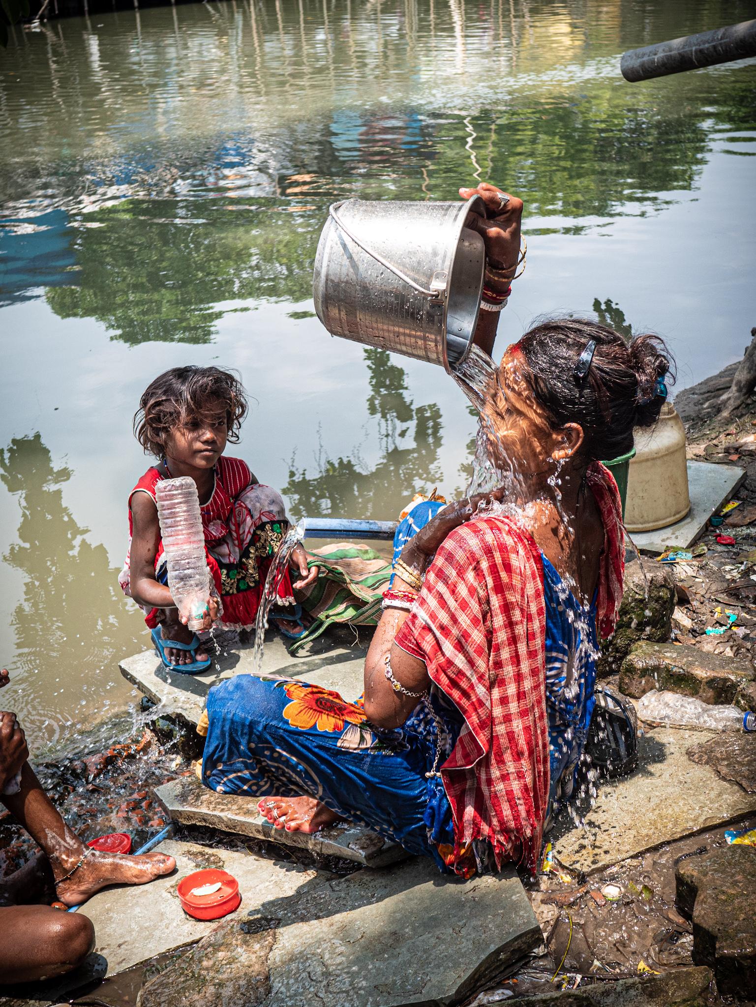 Eine Bewohnerin von Kolkata Station wäscht sich am Kanal.