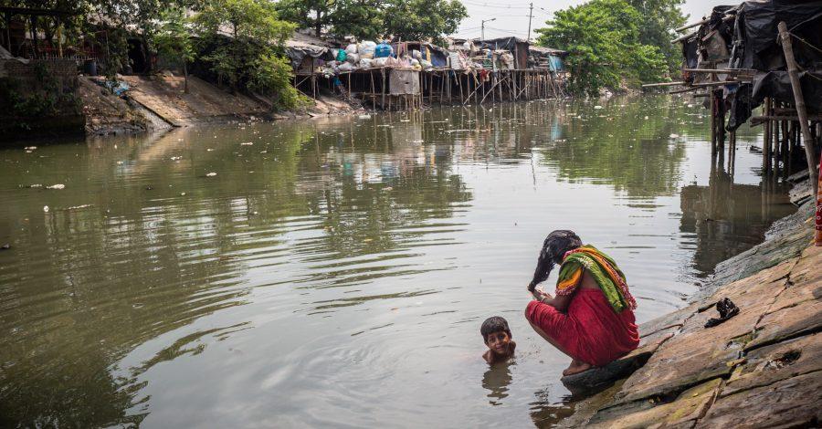 Eine Frau wäscht sich die Haare im Kanal im Slum Kolkata Station und ein Junge badet im Wasser.
